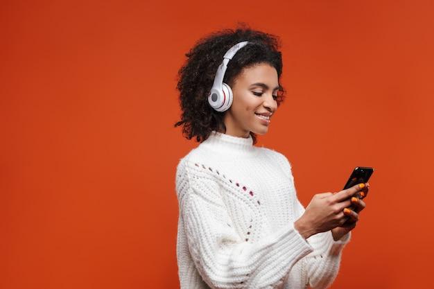 Joyeuse jolie jeune femme africaine portant des écouteurs sans fil, isolée sur un mur rouge, à l'aide d'un téléphone portable