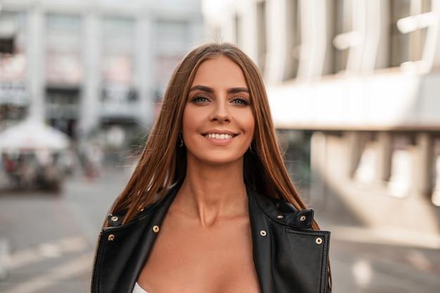 Joyeuse jolie jeune femme aux yeux bleus aux cheveux bruns avec un beau sourire dans une veste en cuir noir à la mode bénéficie d'une promenade autour de la ville par une journée ensoleillée d'automne. portrait d'une belle fille.
