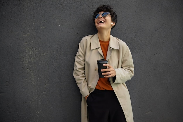 Joyeuse jolie jeune femme bouclée aux cheveux courts foncés riant joyeusement et rejetant la tête en arrière, debout sur l'environnement urbain tout en buvant du café avant la journée de travail