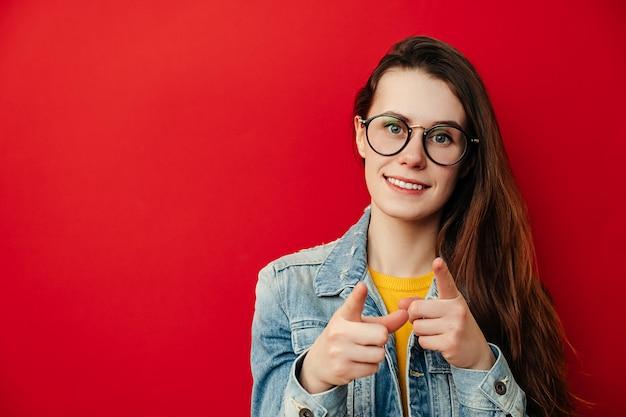 Joyeuse jolie jeune femme à lunettes fait un geste de pistolet à la caméra, exprime le choix, sourit largement, vêtu d'une veste en jean, isolé sur fond rouge avec copie espace