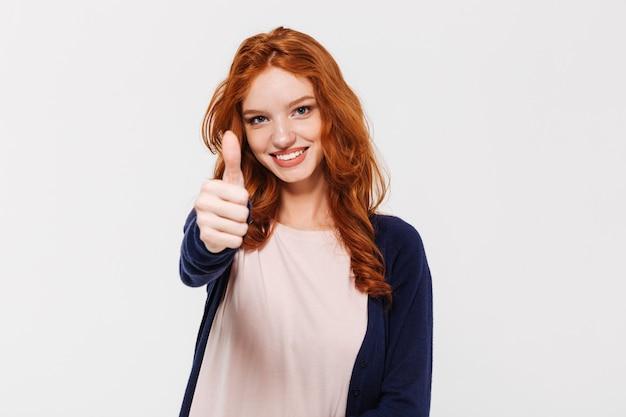Joyeuse jolie jeune femme rousse montrant les pouces vers le haut.