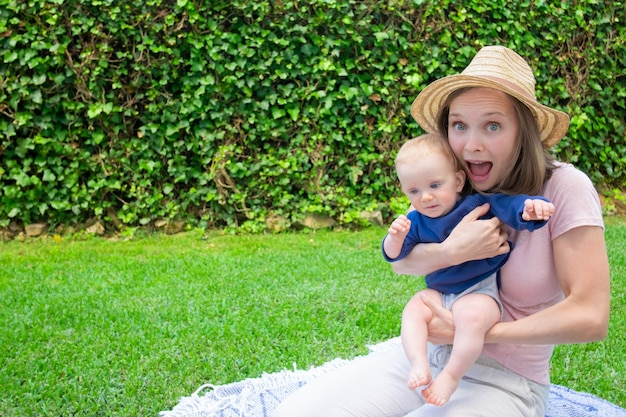 Joyeuse jolie maman assise sur un plaid dans le parc avec la bouche ouverte, tenant le nouveau-né et regardant la caméra. joli bébé en chemise bleue sur les mains de la mère