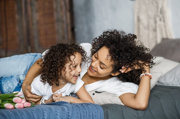 Joyeuse journée de la femme! tulipes maman et fille. maman et fille sourient avec des bretelles d'apparence afro-américaine.