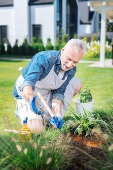 Joyeuse journée. homme mûr barbu portant des gants blancs et un tablier tenant une petite houe dans ses mains tout en essuyant les mauvaises herbes