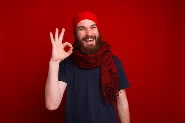 Joyeuse maman barbu, en chapeau rouge et écharpe, montrant signe ok sur l'espace isolé