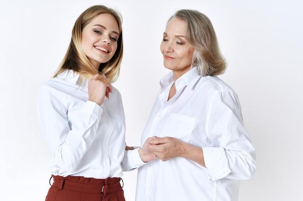 Joyeuse maman et sa fille en chemises blanches embrassent le style de vie