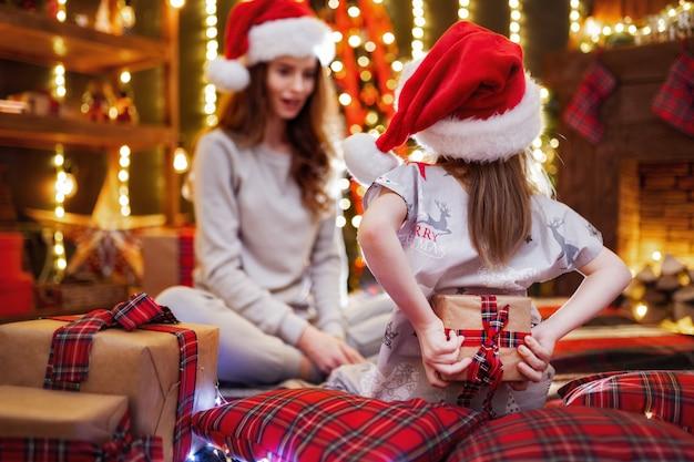 Joyeuse maman et sa fille mignonne échangeant des cadeaux. famille aimante avec des cadeaux dans la chambre de noël.