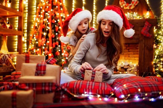 Joyeuse maman et sa fille mignonne échangeant des cadeaux. parent et petits enfants s'amusant près de l'arbre à l'intérieur. famille aimante avec des cadeaux dans la chambre de noël.