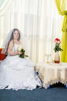 Une joyeuse mariée juive avec son visage recouvert d'un voile avec un bouquet de roses blanches est assise dans une synagogue avant d'accomplir le rite huppa à une table avec des fleurs. photo verticale