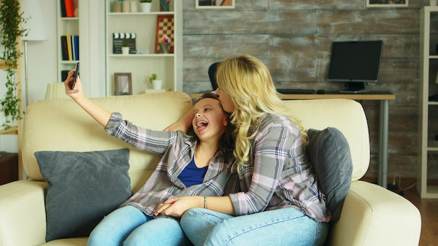 Joyeuse mère et fille prenant un selfie avec un smartphone dans le salon.