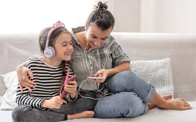 Joyeuse mère et fille se reposent à la maison, écoutant de la musique sur des écouteurs