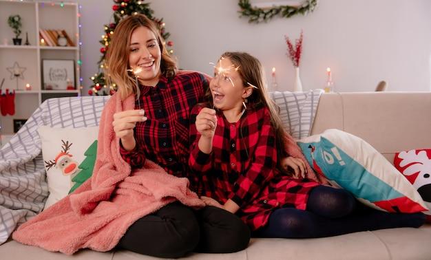 Joyeuse mère et fille tenant des cierges recouverts d'une couverture assis sur un canapé et profiter de noël à la maison