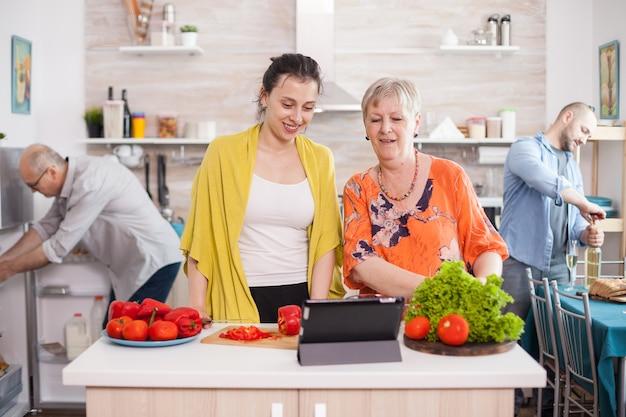 Joyeuse mère et fille utilisant une tablette pour cuisiner une salade savoureuse en suivant la recette en ligne dans la cuisine. mari tenant une bouteille de vin. père regardant à l'intérieur du réfrigérateur