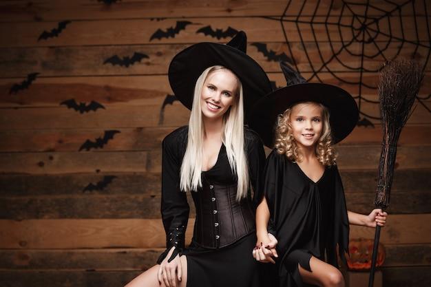 Joyeuse mère et sa fille en costumes de sorcière célébrant halloween posant avec des citrouilles courbées