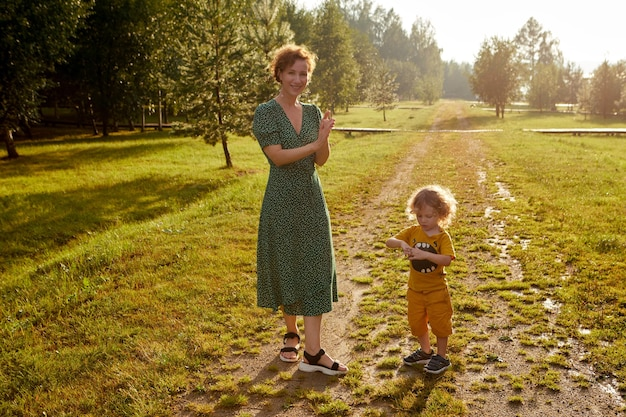 Joyeuse mère avec son fils debout sur un sentier herbeux