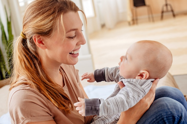 Joyeuse mère tenant son bébé à la maison