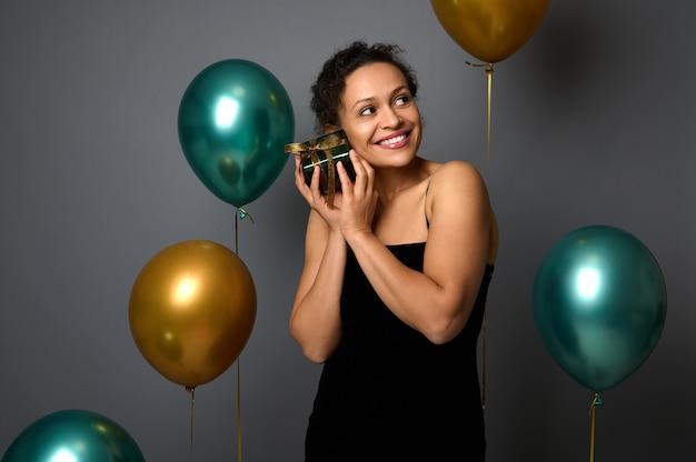 Joyeuse métisse jolie femme avec un beau sourire tient une boîte-cadeau près de son visage, pose sur fond gris avec des ballons à air vert doré. concepts d'anniversaire, de noël, de nouvel an pour la publicité.