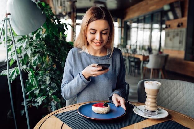 Joyeuse nicegirl prenant la photo de savoureux gâteau sur le téléphone mobile, passer du temps au café