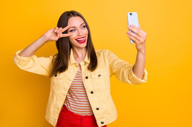 Joyeuse petite amie montrant v-sign prenant selfie à l'étranger léchant la lèvre supérieure mur de couleur vive isolé
