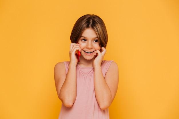 Joyeuse petite dame parlant au téléphone isolé