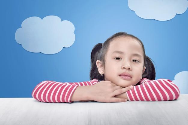 Joyeuse petite fille asiatique se détendre sur la table