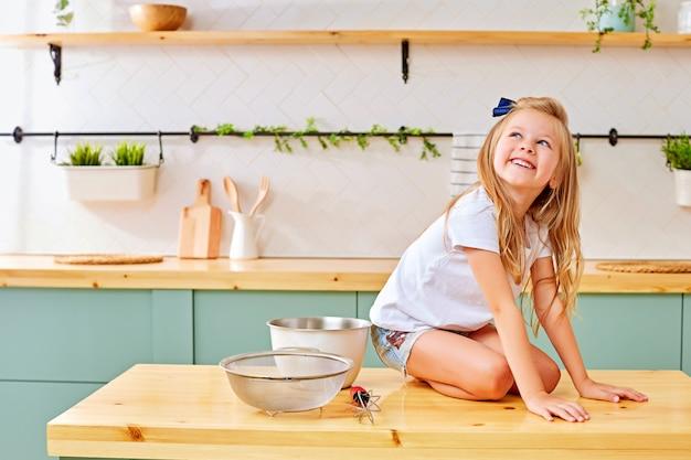 Joyeuse petite fille assise sur la table de la cuisine