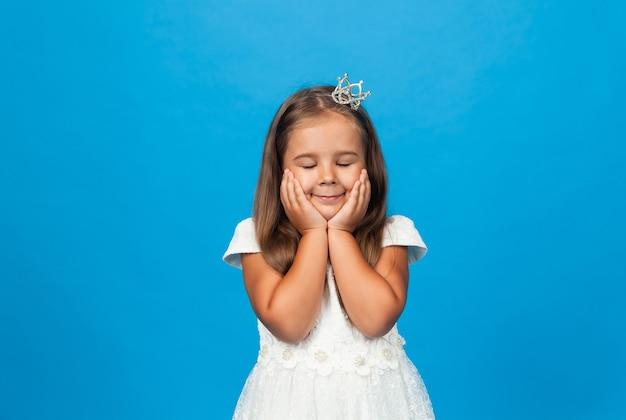 Joyeuse petite fille aux cheveux longs dans une robe de princesse et avec une couronne.