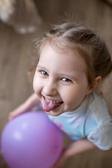 Joyeuse petite fille avec un ballon dans ses mains rit et montre sa langue.