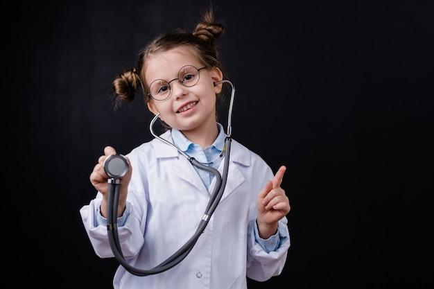 Joyeuse petite fille en blanchon à l'aide d'un stéthoscope tout en vous pointant devant la caméra contre l'espace noir