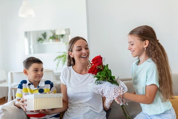 Joyeuse petite fille avec bouquet de fleurs roses et plus jeune frère avec boîte-cadeau souriant et félicitant l'heureuse maman le jour de la fête des mères à la maison. bonne fête des mères!
