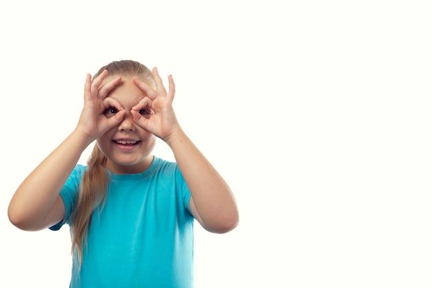 Joyeuse petite fille caucasienne dans un t-shirt bleu fait des lunettes avec ses doigts sur fond blanc