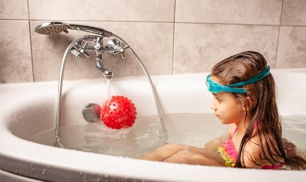 Joyeuse petite fille charmante souriante baigne avec une boule rouge