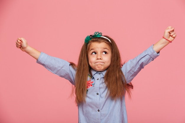 Joyeuse petite fille dans le cerceau de cheveux avec les lèvres pincées mettant les poings serrés les bras en l'air