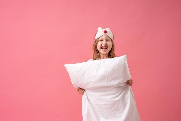 Joyeuse petite fille dans un masque de sommeil regarde derrière un oreiller