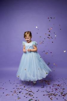 Une joyeuse petite fille dans une robe de princesse bleue danse sur violet