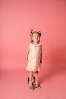 Une joyeuse petite fille dans une robe de vacances rose se tient dans les chaussures de sa mère sur une surface rose avec une place pour le texte