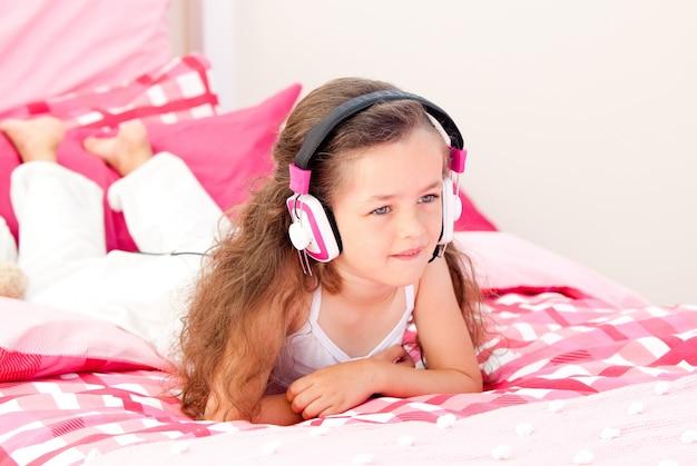 Joyeuse petite fille écoute musique allongée sur son lit