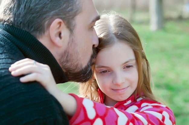 Joyeuse petite fille embrassant son père et à la recherche