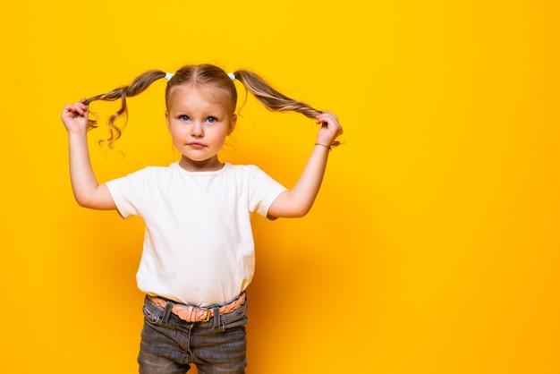 Joyeuse petite fille jouant avec les cheveux posant isolé sur mur jaune