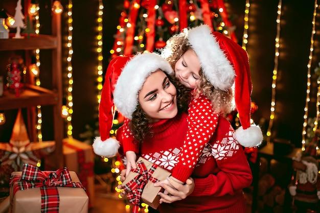 Joyeuse petite fille mignonne et sa sœur aînée échangeant des cadeaux