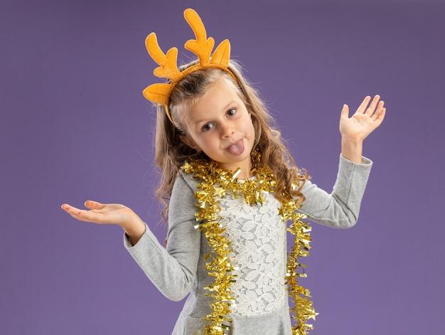 Joyeuse petite fille portant un cerceau de cheveux de noël avec guirlande sur le cou écartant les mains et montrant la langue isolée sur fond bleu
