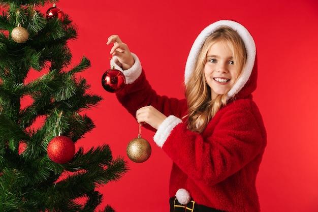Joyeuse petite fille portant le costume de noël debout isolé, décoration de l'arbre de noël