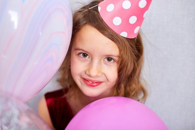 Joyeuse petite fille en robe rose et chapeau joue avec des ballons à la fête d'anniversaire