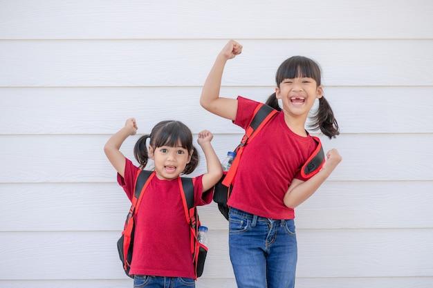 Joyeuse petite fille souriante avec un gros sac à dos sautant et s'amusant contre le mur blanc. en regardant la caméra. notion d'école. retour à l'école