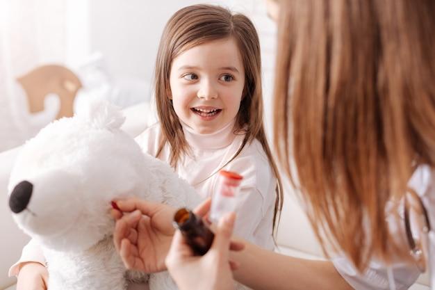 Joyeuse petite fille tenant son jouet moelleux pendant que sa mère se faisant passer pour un médecin et donnant des pilules