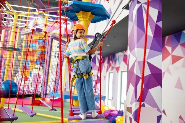 Joyeuse petite fille sur la tyrolienne au centre de divertissement. enfants s'amusant dans la zone d'escalade, les enfants passent le week-end sur l'aire de jeux, enfance heureuse
