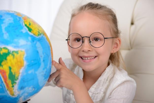 Joyeuse petite fille en vetu examinant le globe.