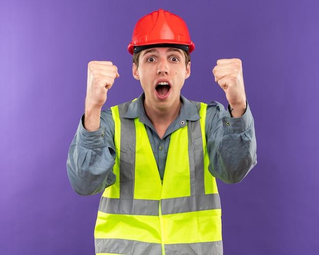 Joyeuse Regardant La Caméra Jeune Homme De Construction En Uniforme Montrant Un Geste Oui Photo gratuit