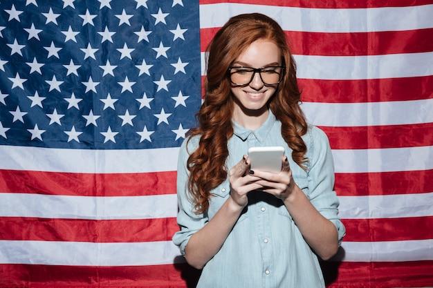 Joyeuse rousse jeune femme debout sur le drapeau des états-unis bavarder