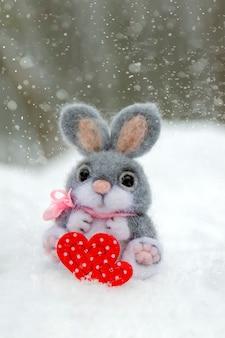 Joyeuse saint valentin carte de voeux ou bannière lapin en peluche tenant un coeur rouge symbole de vacances d'amour...